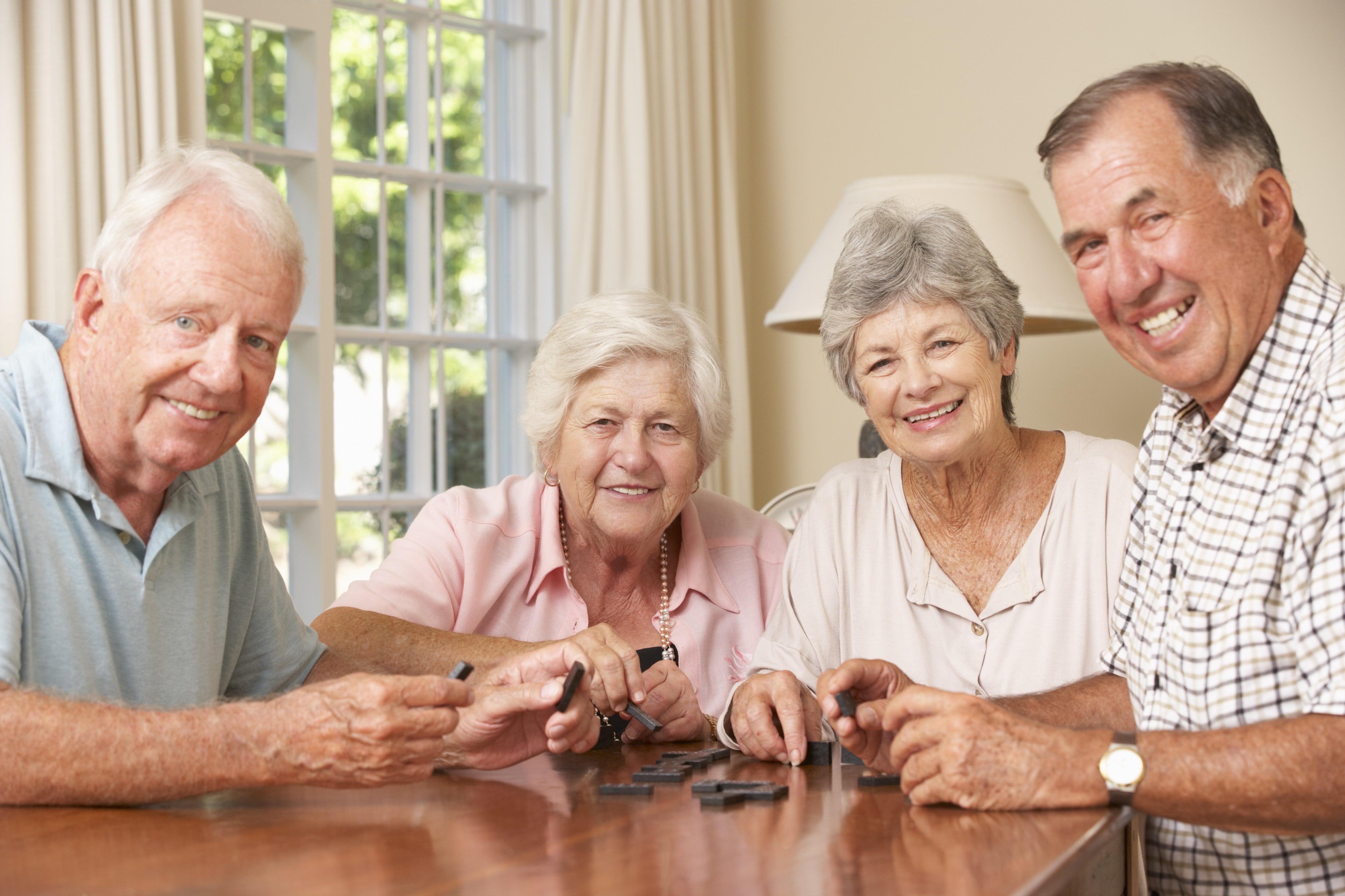 vier Senioren spielen Domino