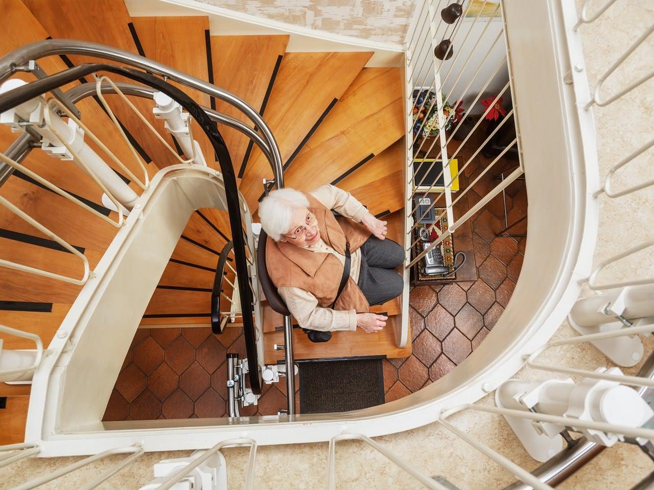 Ältere Frau fährt mit einem Treppenlift
