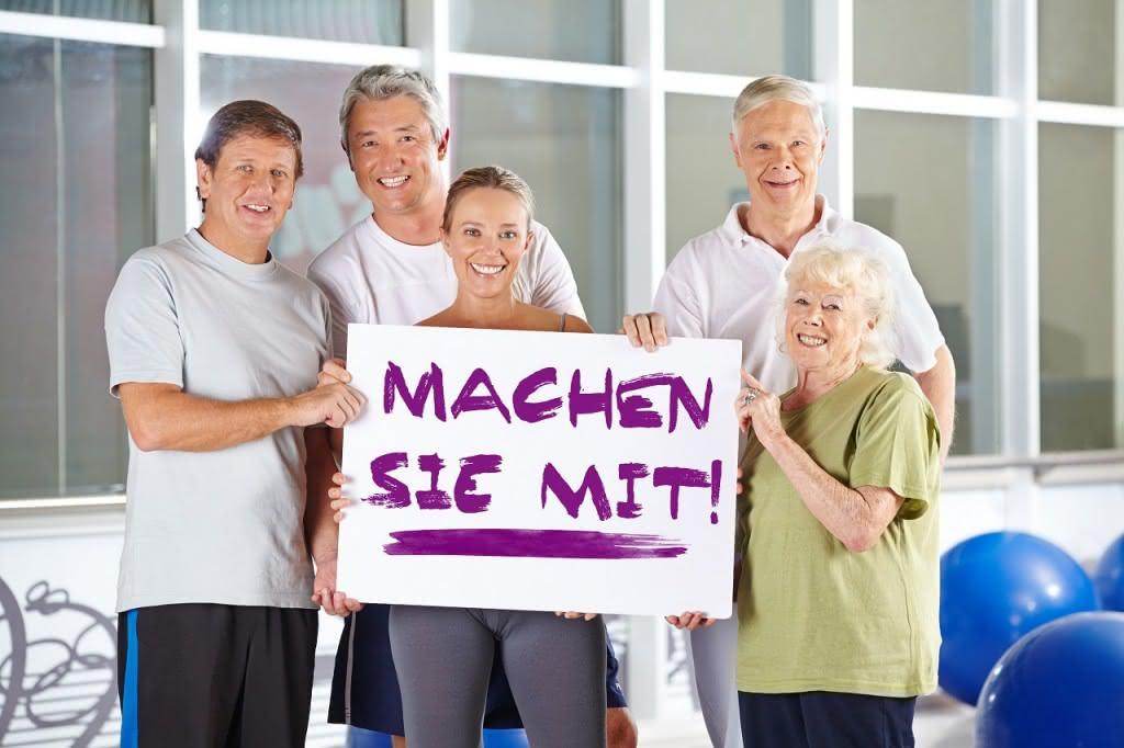 """Gruppe Senioren hält """"Machen sie mit"""" Schild im Fitnesscenter"""