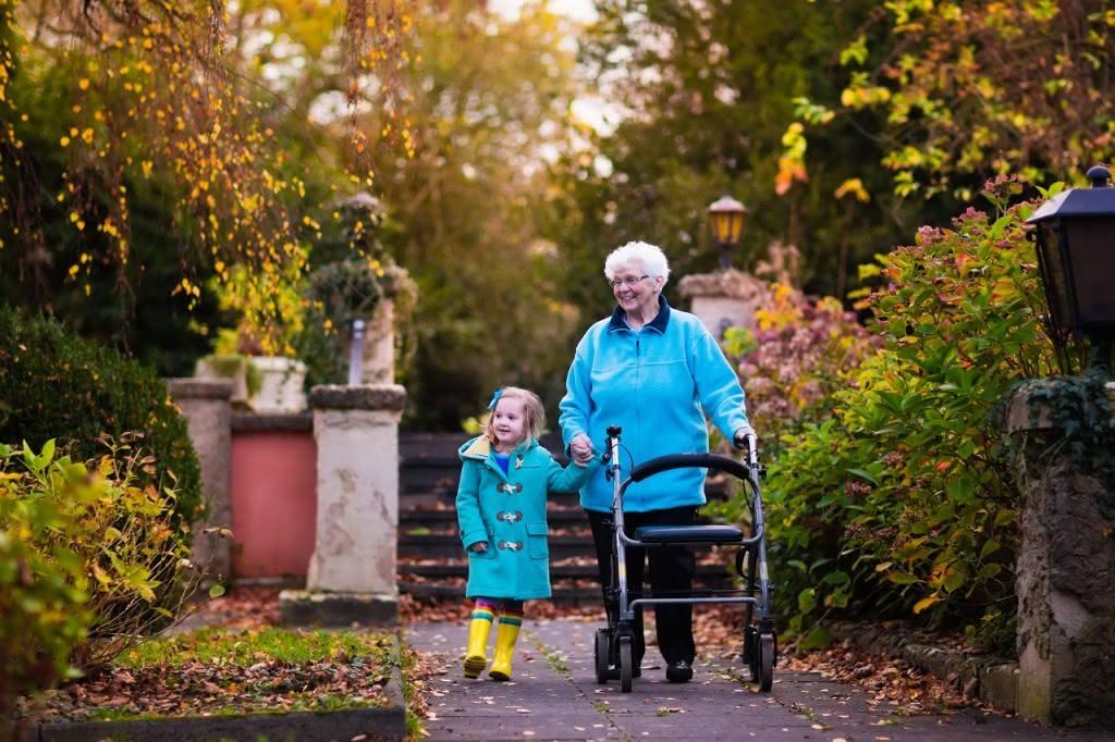 Oma mit Rollator und Enkelin gehen spazieren