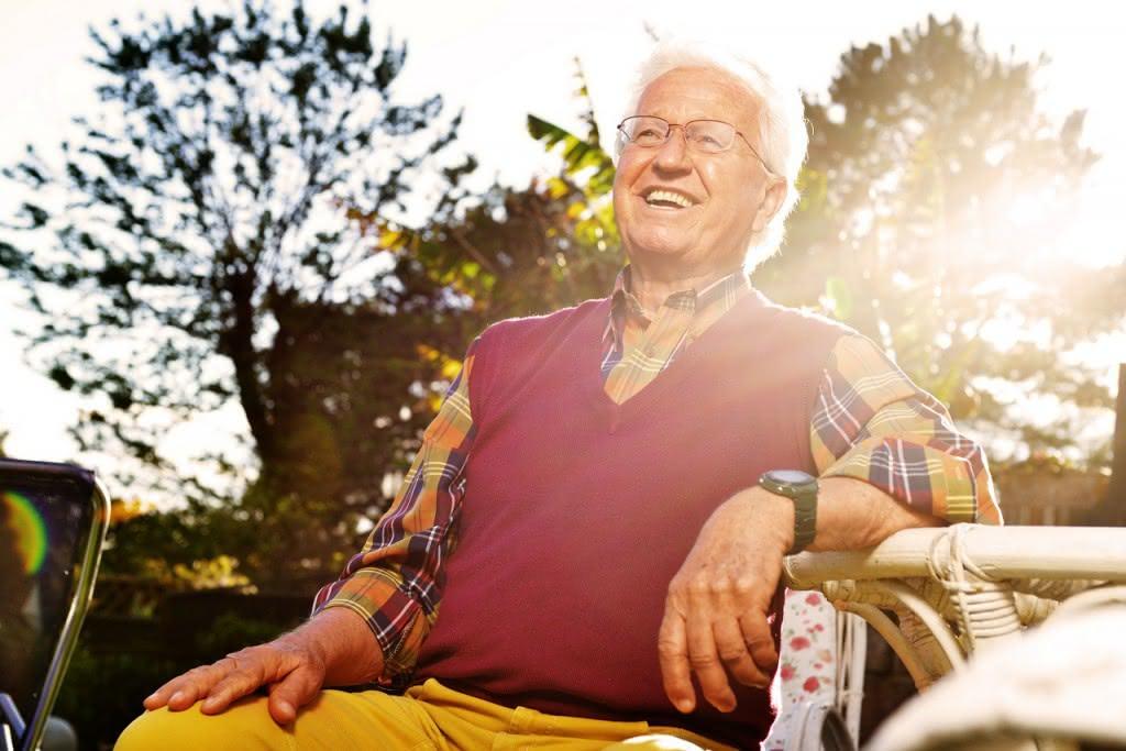 Mann sitzt im Sonnenschein im Garten