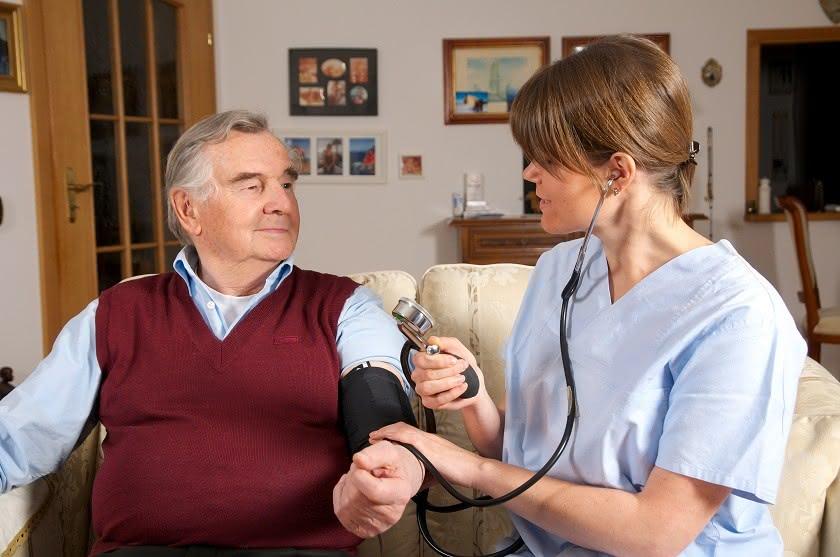 Ambulante Pflegerin misst Blutdruck beim Rentner