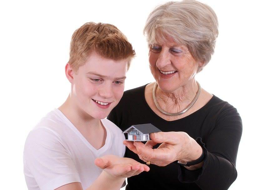 Seniorin gibt Junge ein Miniaturhaus Sinnbild für Erbe