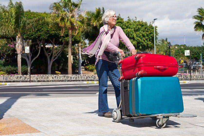 Seniorin mit Koffern auf dem Flughafenvorplatz