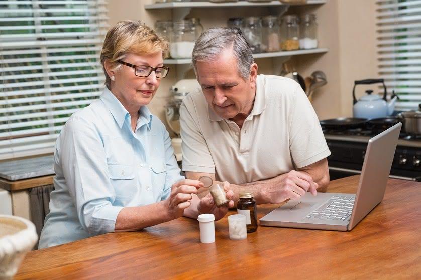 Rentnerpaar mit Laptop und Medikamenten