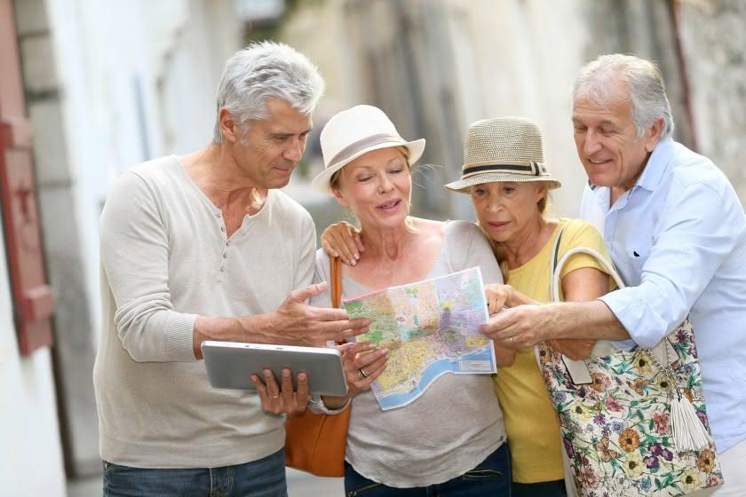 Vier Senioren mit Stadtplan in einer Straße