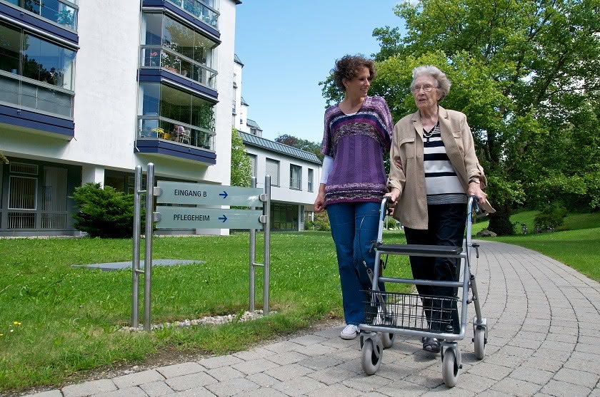 Seniorin und junge Frau vor Seniorenheim