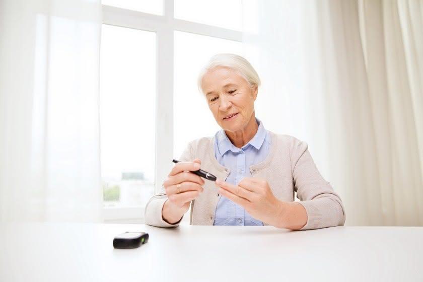 Seniorin sitzt am Tisch und misst am Finger den Blutzucker