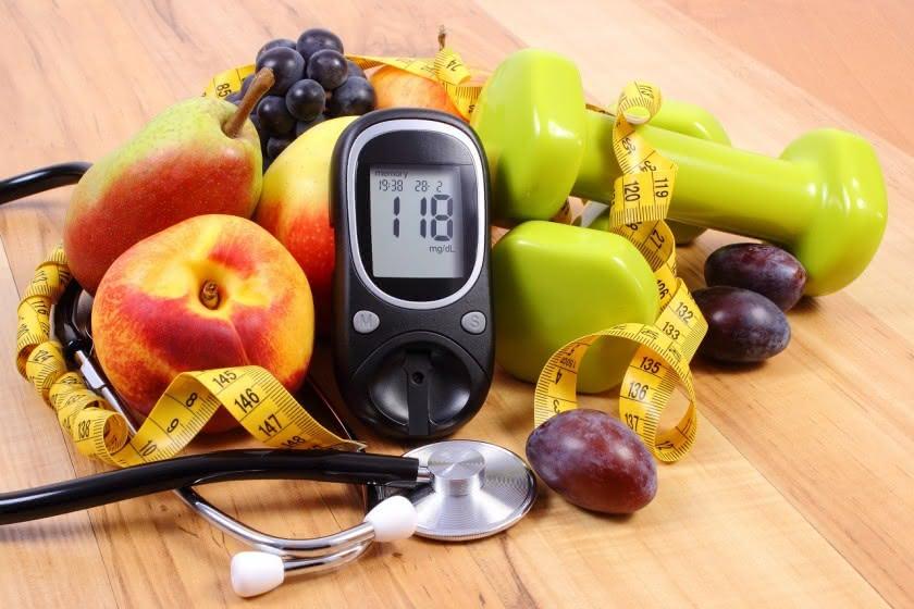 Blutdruckmessgerät umgeben von Obst, Stethoskop und Maßband