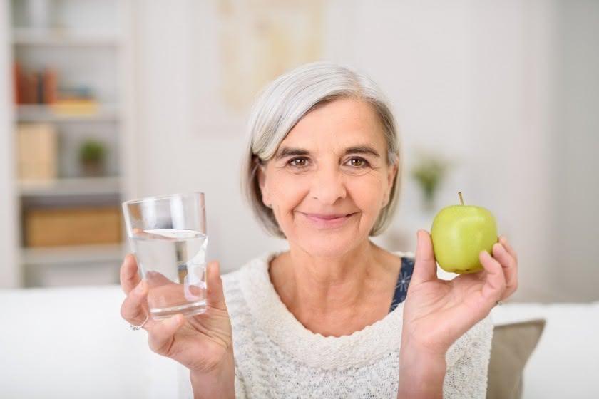 Seniorin hält Wasserglas und Apfel in den Händen