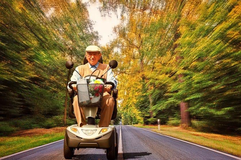 Senior mit Scooter auf herbstlicher Straße