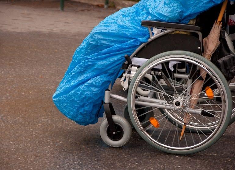Person im Rollstuhl mit Beinschutzdecke