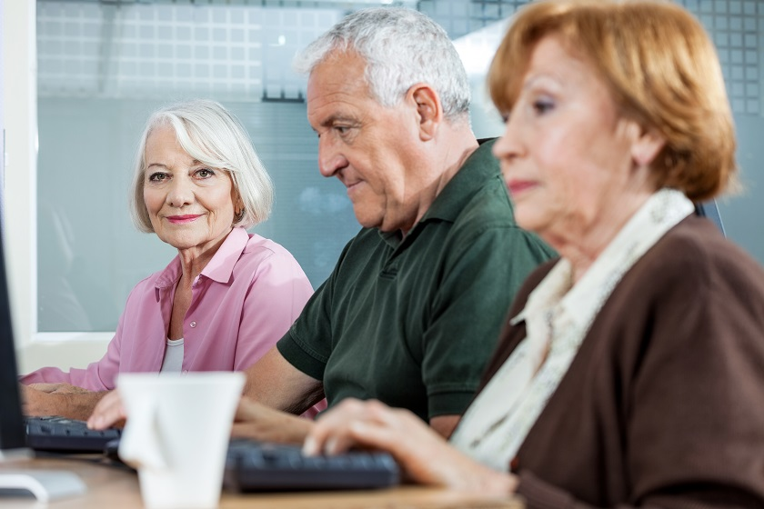 drei Senioren nutzen Computer in einem Klassenraum
