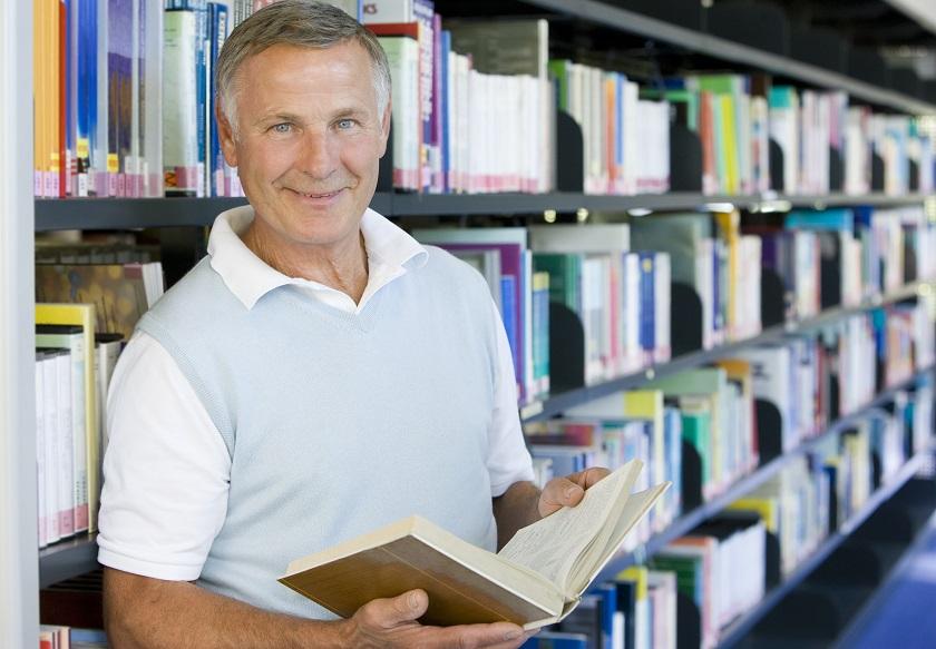 Rentner liest ein Buch in einer Bibliothek