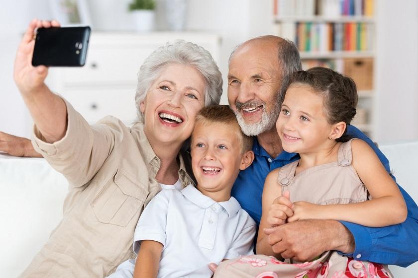 Seniorenpaar fotografiert sich und zwei Enkelkinder mit dem Smartphone