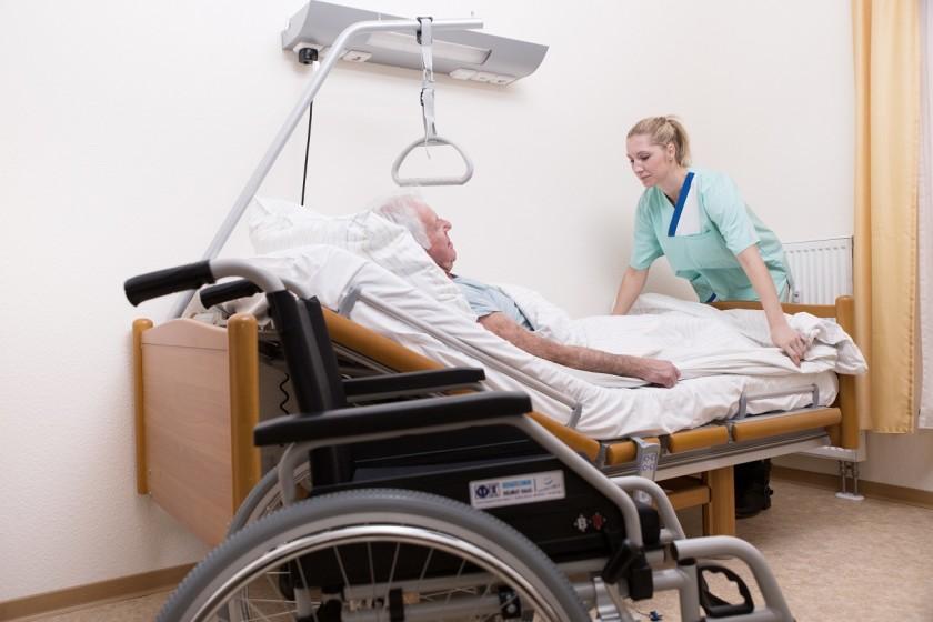 Bettlägeriger Mann mit Pflegerin