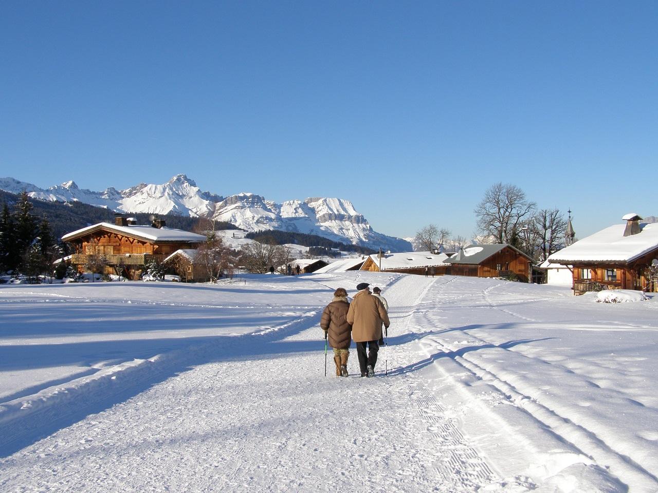 Senioren Paar geht auf einer verschneiten Straße vor Bergpanorama entlang