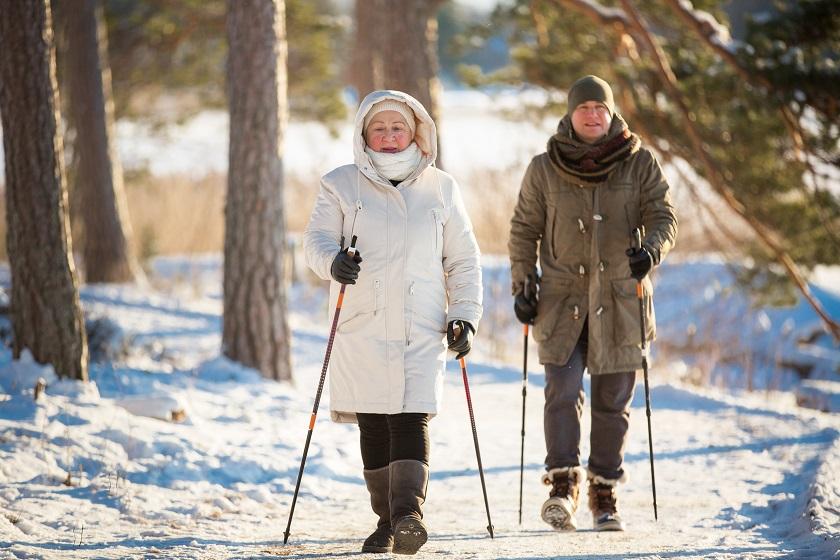 Zwei Senioren gehen mit Stöcken im Schnee spazieren