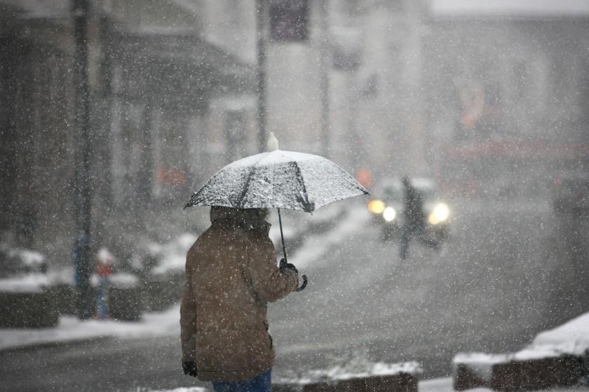 Winter Wetter Mann mit Schirm im Schnee
