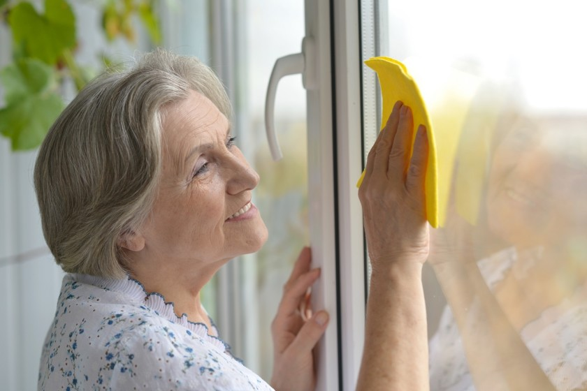 Seniorin beim Frühjahrsputz am Fenster
