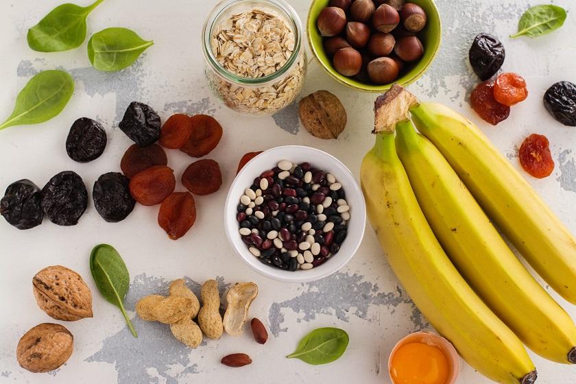 Bananen, Nüsse, Haferflocken, Pflaumen, EI auf einer weißen Oberfläche