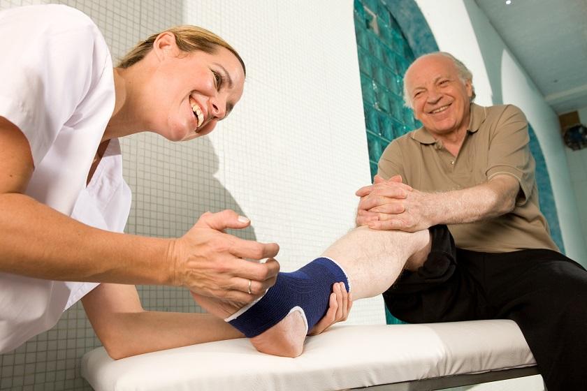 Senior mit Fußbandage bei der Physiotherapie
