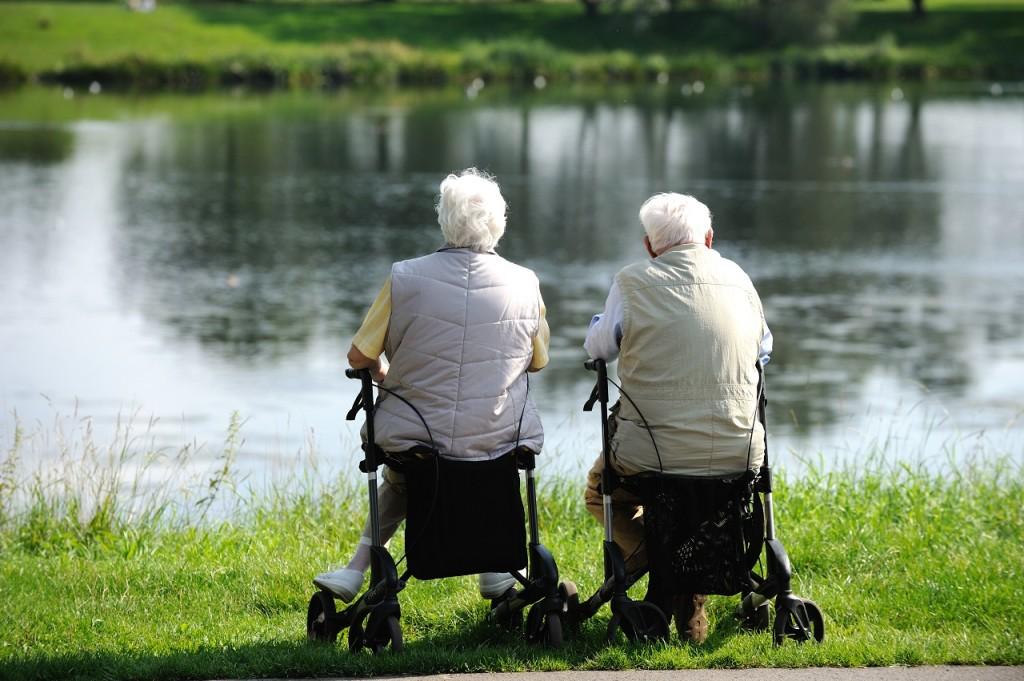 Renterpaar sitzen auf Rollatoren und schauen auf einen See