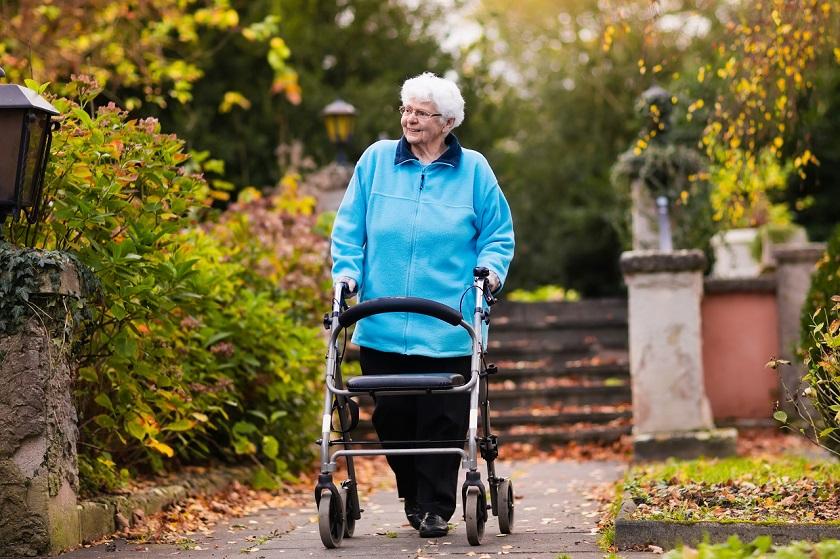 Seniorin spaziert mit Rollator im Park