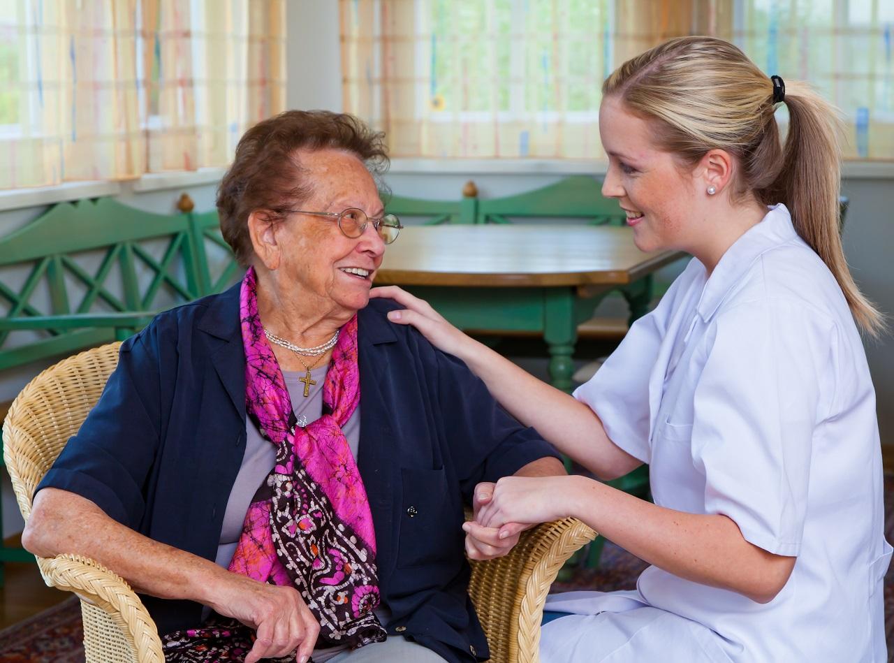 Pflegerin der Hauskrankenpflege besucht eine Patientin