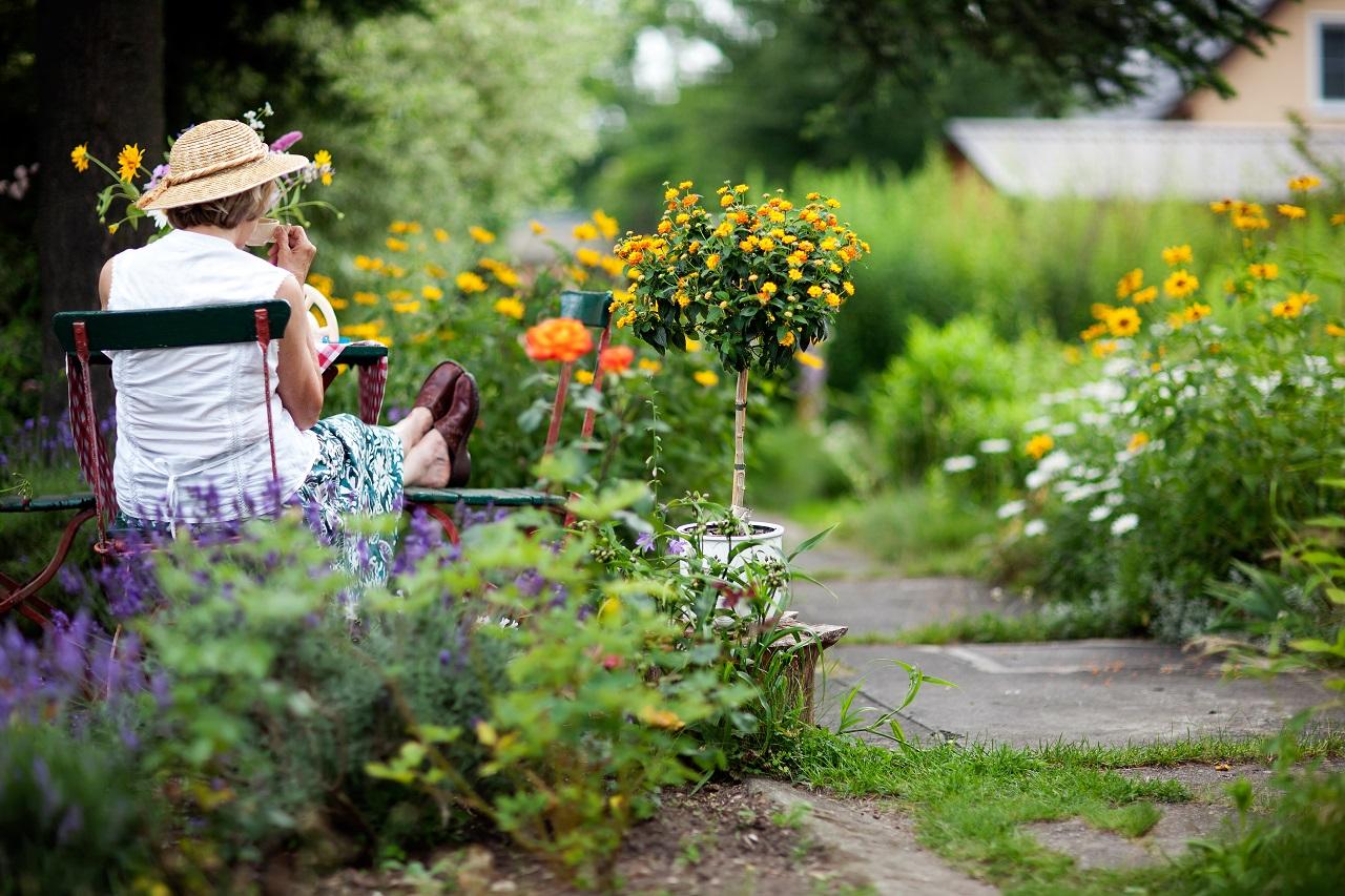 Seniorin entspannt sich auf einem Stuhl im Garten bei einem Getränk