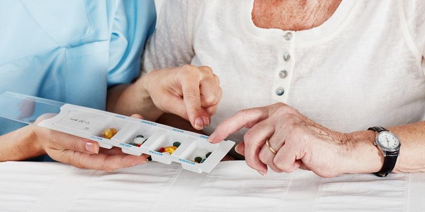 Pflegerin sieht sich mit Seniorin Tablettenbox an