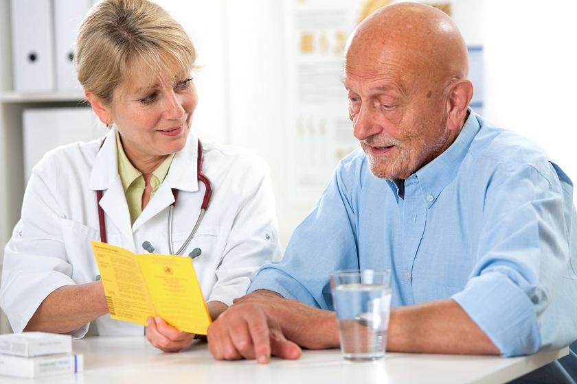 Senior mit Impfpass beim Arzt