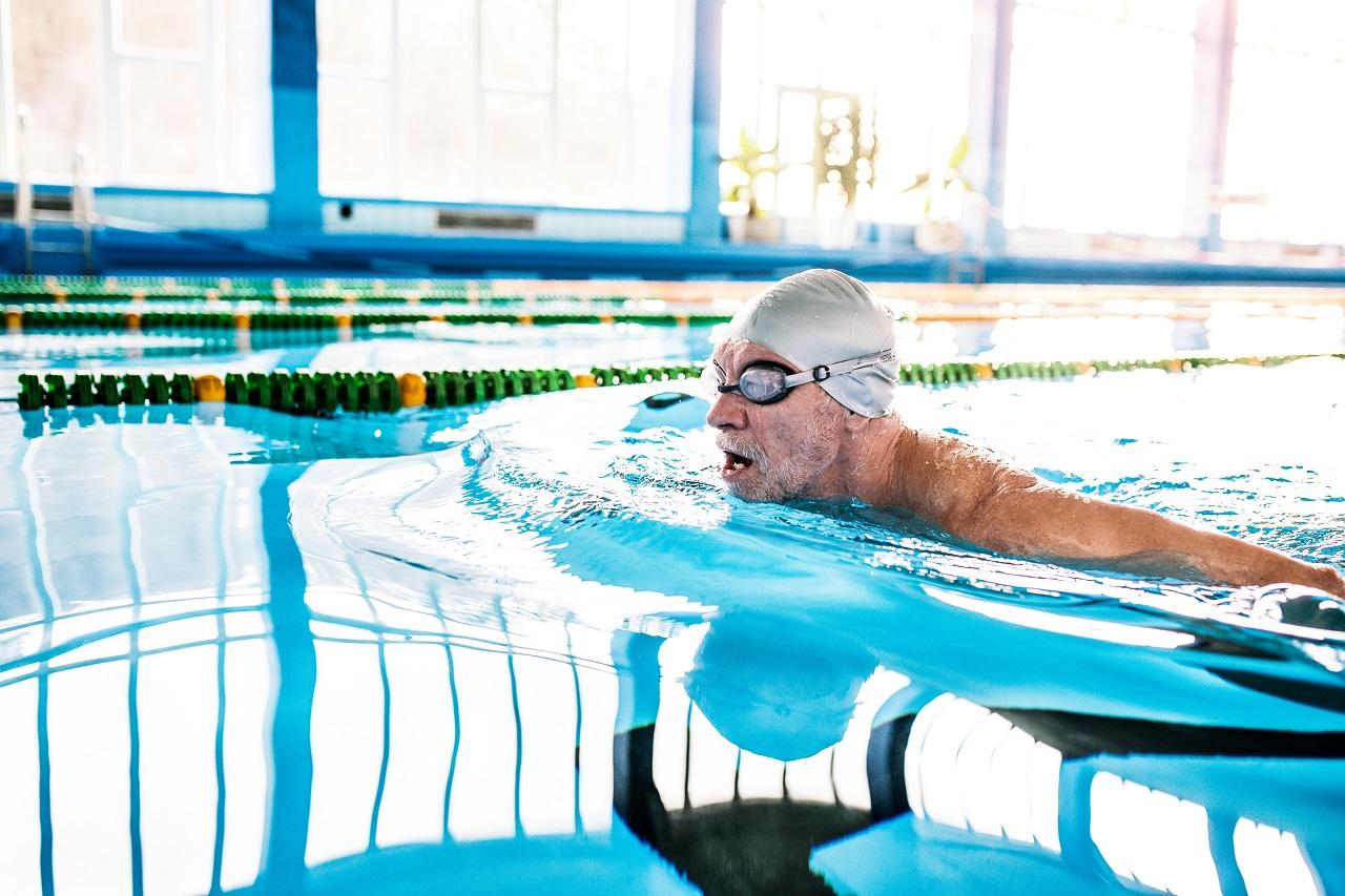 Senior schwimmt mit Badekappe