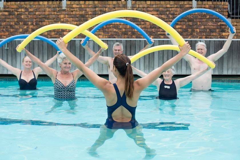 Senioren Aqua Fitness Kurs im Schwimmbad - Übung mit Poolnudel