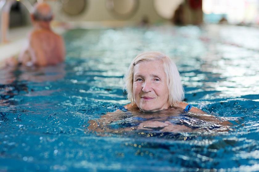 Seniorin schwimmt im Schwimmbad