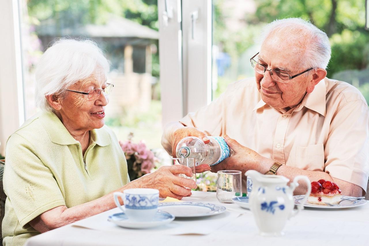 Älteres Paar trinkt Wasser am Tisch