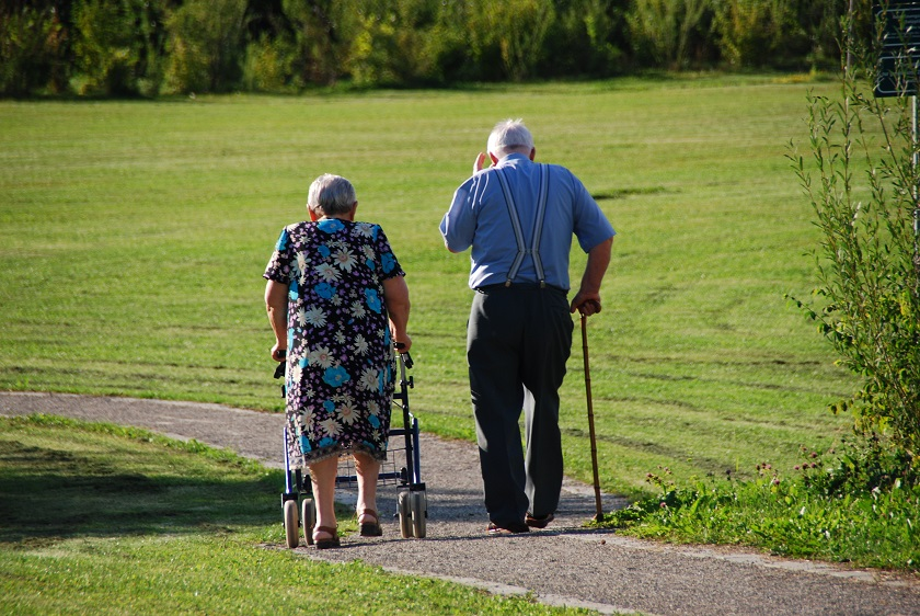 Älteres Paar geht mit Rollator und Gehstock spazieren