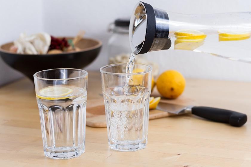 Zwei Gläser und eine Karaffe mit Wasser und Zitronenscheiben