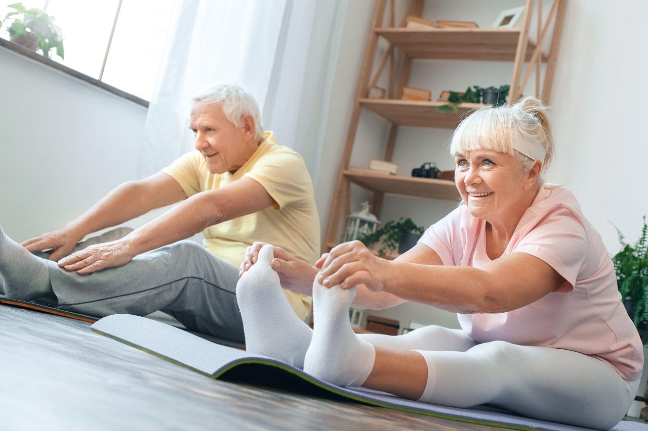 Älteres Paar macht Sport auf Yogamatten im Wohnzimmer