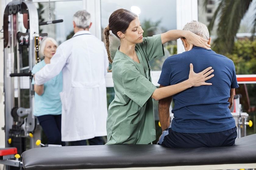 Älteres Paar beim Arzt und Physiotherapeutin