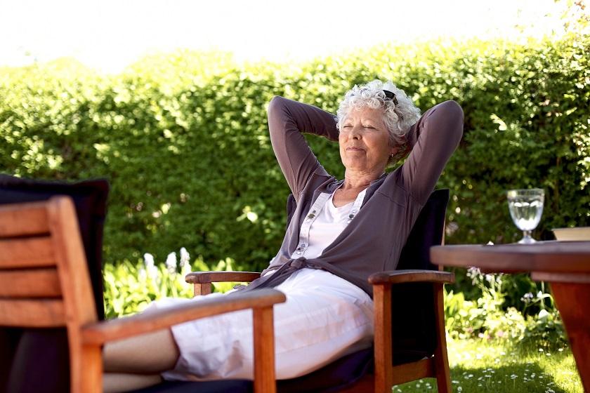 Ältere Frau entspannt im Garten im Sommer
