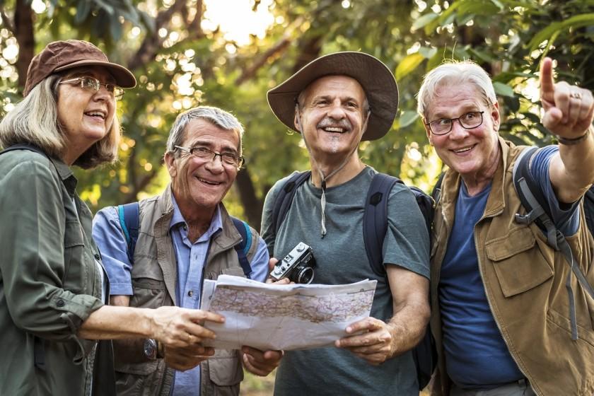 Vier Senioren im Wald mit Landkarte