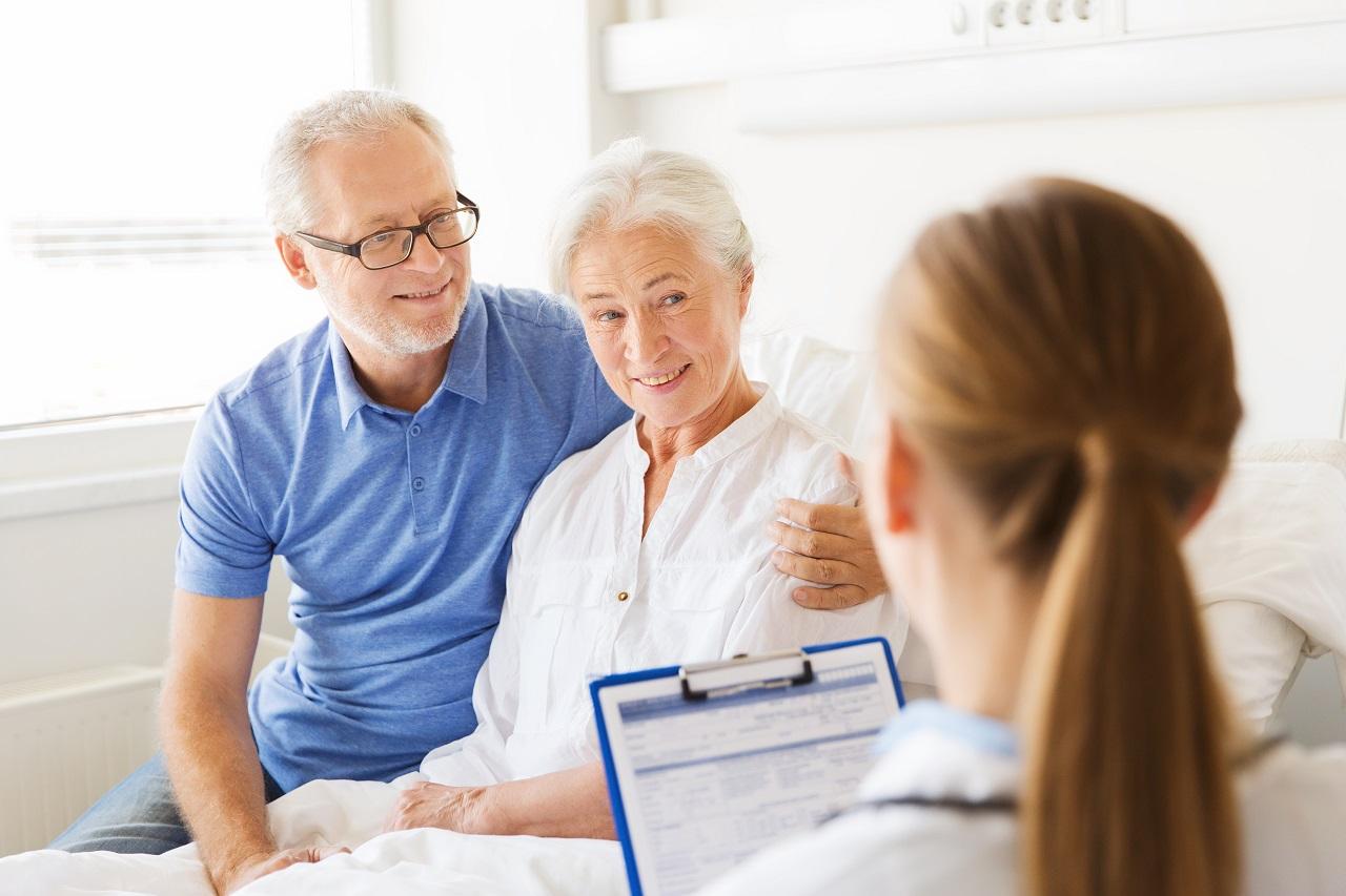 Seniorin im Krnakenhaus mit Arzt und Angehörigem