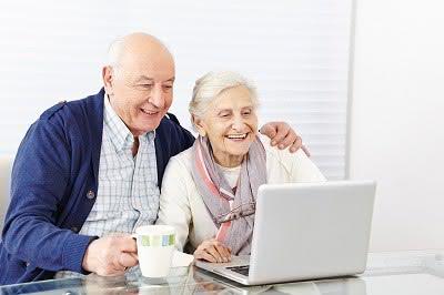 Lachendes Paar Senioren surft gemeinsam am Computer im Internet