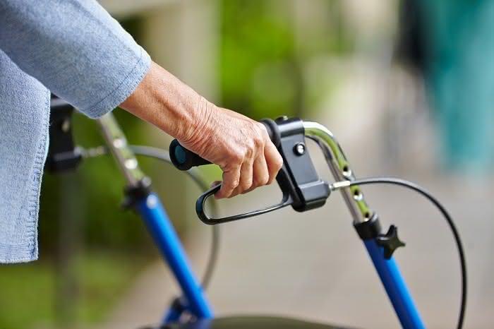 Hände eines Senioren am Griff eines Rollators