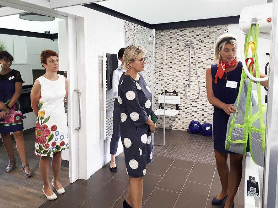Mitarbeiterin des ubineum erklärt Staatsministerin Klepsch im Vorführbad die Funktion des Patientnliftes.