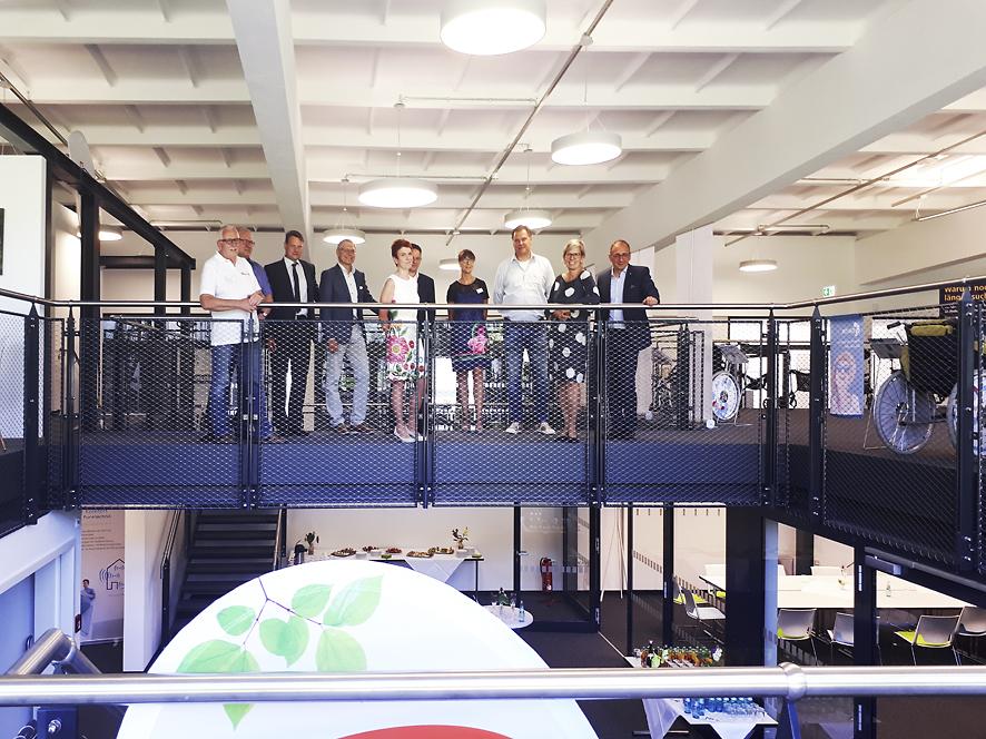 Männer und Frauen stehen auf der oberen Etage am Galeriegeländer im ubineum.